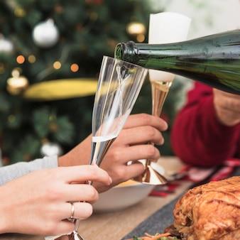 Persona vertiendo champán en copa en mesa navideña