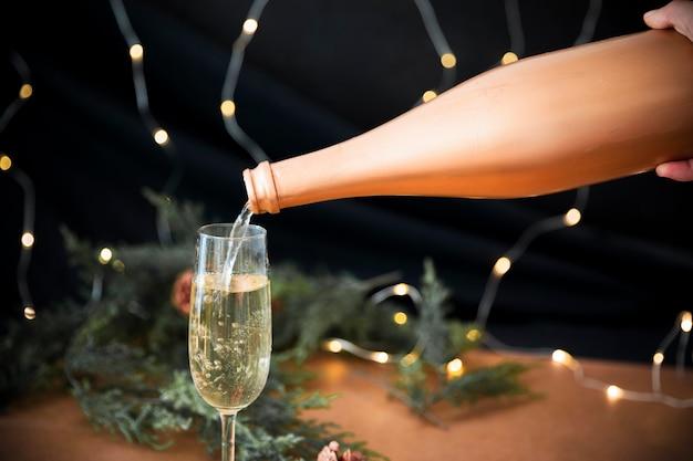 Persona vertiendo champán en copa