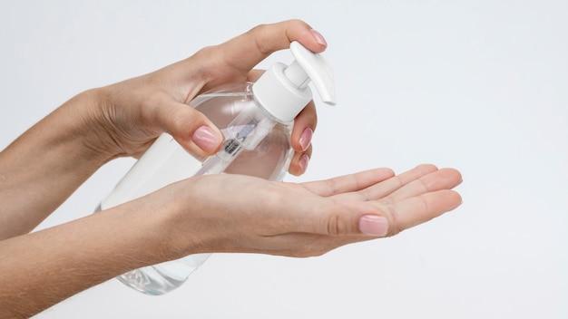 Persona vertiendo jabón líquido de una botella con espacio de copia