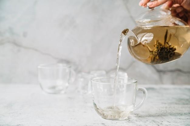 Persona vertiendo té en tazas vista frontal