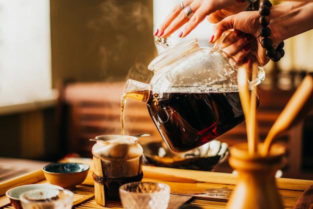 Persona vierte té verde fresco en café