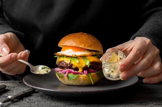 Persona de la vista frontal cerca de la hamburguesa en el plato que sostiene el frasco con mantequilla