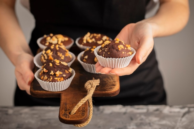 Persona de vista frontal sosteniendo cupcakes dulces