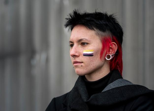 Persona de vista lateral que tiene una bandera no binaria pintada en la mejilla