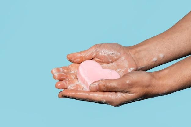 Persona de vista lateral sosteniendo un jabón en forma de corazón