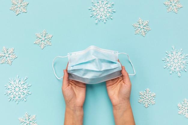 Persona de la vista superior con máscara médica cerca de copos de nieve decorativos
