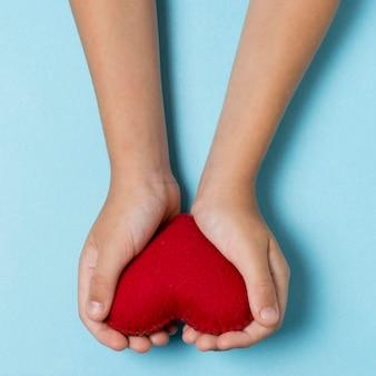 Persona de vista superior sosteniendo un corazón rojo