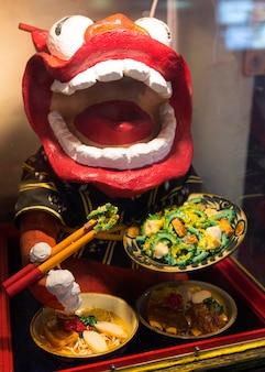 Personaje de dragón chino presentando comida tradicional.
