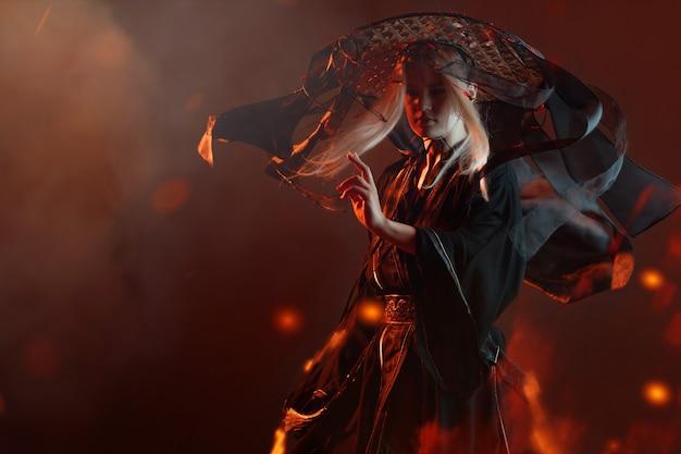 Un personaje de estilo asiático con un kimono y un sombrero de paja con cintas entre el fuego
