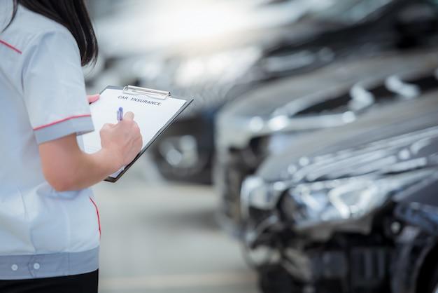 El personal del agente de seguros escribe en el portapapeles mientras revisa el automóvil después de ser evaluado y procede a reclamar el accidente: el automóvil tiene seguro contra accidentes.