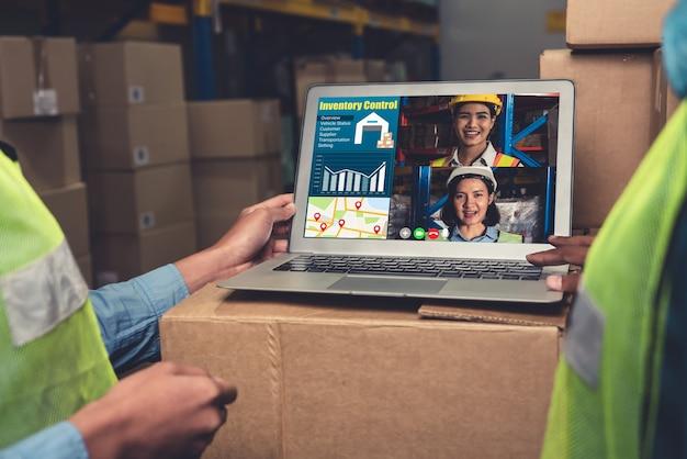 El personal del almacén hablando por videollamada en la pantalla de la computadora en el almacén de almacenamiento