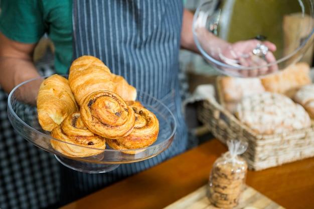 Personal con bandeja de croissant en el mostrador