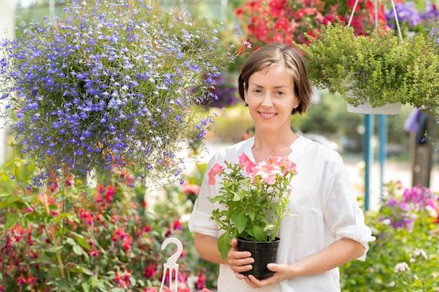 Personal de centro de jardinería bastante femenino con ramo de petunias en manos de pie