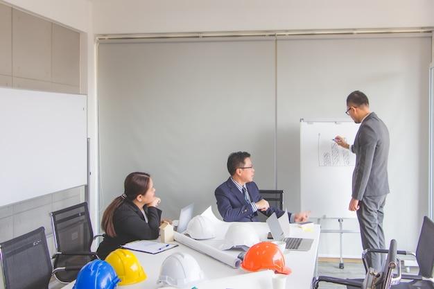 El personal de contabilidad está dibujando el último gráfico de ganancias trimestrales para el jefe de departamento por la mañana en la sala de reuniones. en el concepto de operación de una empresa constructora
