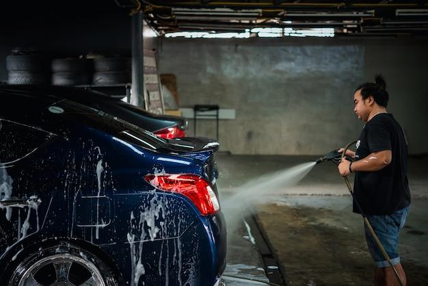 Personal de cuidado del automóvil no identificado que limpia (limpia, lava, pule, encera y recubrimiento de vidrio) el automóvil (detalles del automóvil) en el taller de cuidado del automóvil