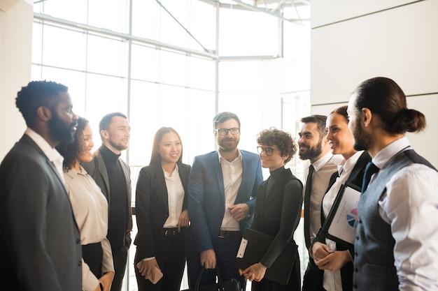 El personal de la empresa moderna de pie en círculo y haciendo una lluvia de ideas sobre la estrategia de desarrollo en la oficina