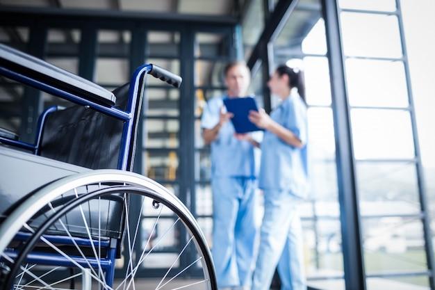 Personal de enfermería trayendo una silla de ruedas en el hospital