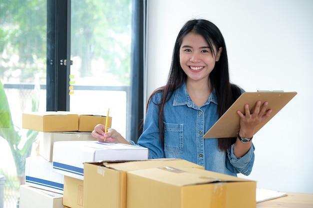 El personal de entrega está marcando la caja del producto para entregar al cliente.