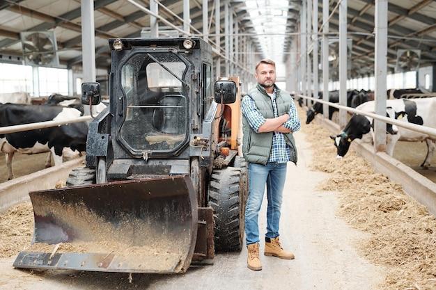 El personal exitoso de una granja contemporánea cruza los brazos al pecho mientras está de pie junto al tractor frente a las vacas lecheras