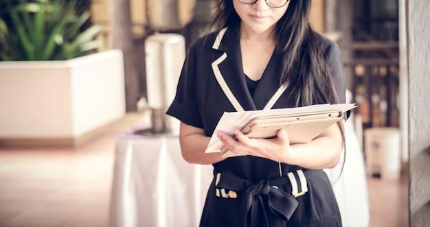 El personal femenino está analizando los documentos del informe en la mano.