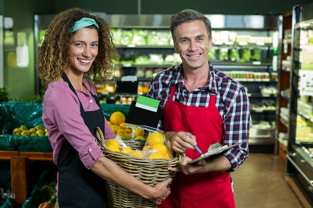 Personal femenino con cesta de frutas y personal masculino con portapapeles en supermercado