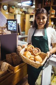 Personal femenino con croissant en cesta de mimbre en mostrador de pan