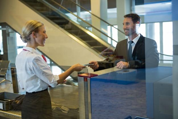 Personal femenino dando tarjeta de embarque al empresario