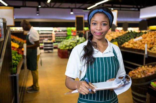 Personal femenino escribiendo en el bloc de notas en el supermercado