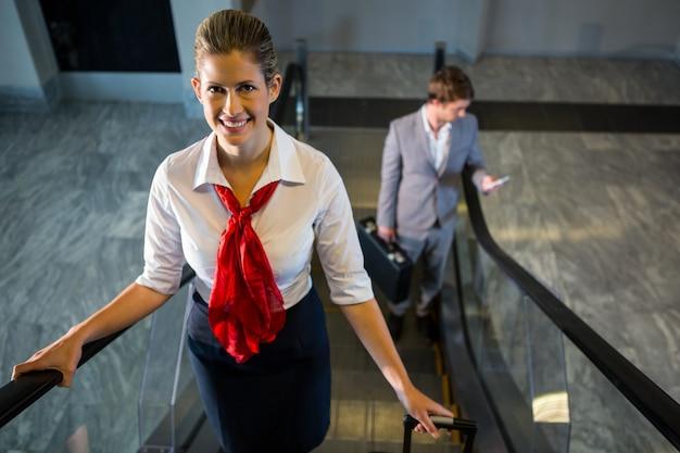 Personal femenino y pasajeros con equipaje en escaleras mecánicas