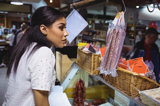 Personal femenino pensativo de pie en el mostrador de carne
