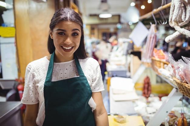 Personal femenino de pie en el mostrador de carne