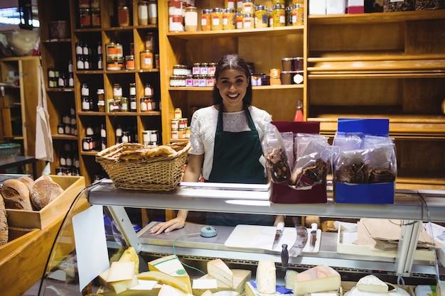 Personal femenino de pie en el mostrador de queso