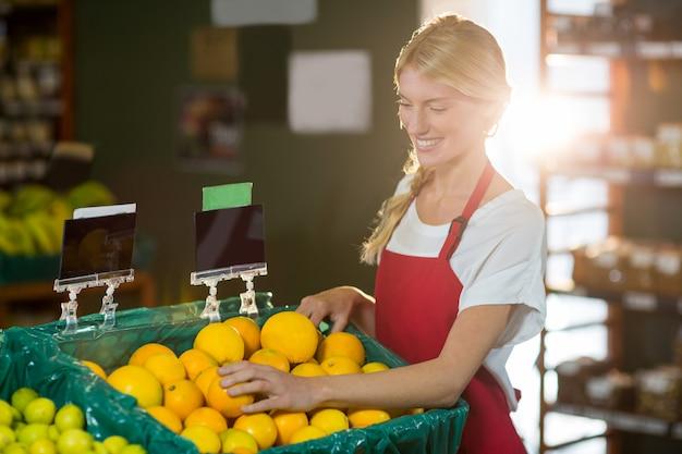 Personal femenino que controla frutas en la sección orgánica