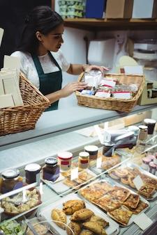 Personal femenino que trabaja en el mostrador de alimentos