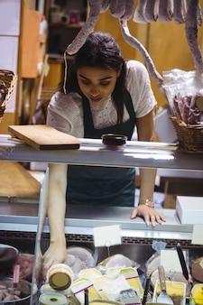 Personal femenino que trabaja en el mostrador de carne