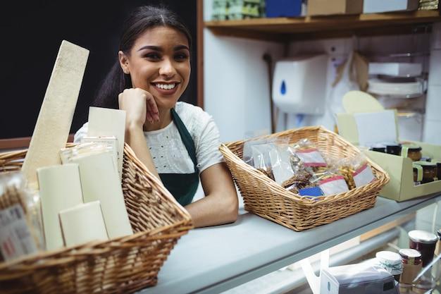 Personal femenino sonriendo en mostrador de comida