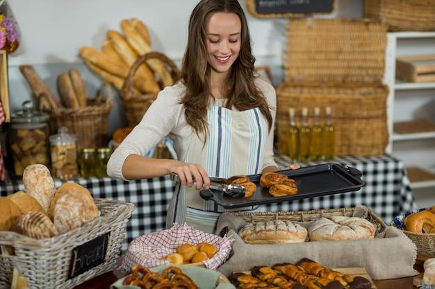 Personal femenino sonriente colocando croissant en la bandeja en el mostrador
