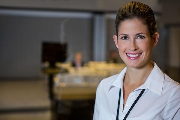 Personal femenino sonriente de pie en el aeropuerto