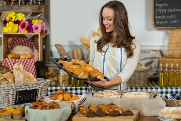 Personal femenino sonriente que sostiene la bandeja de panes en el mostrador