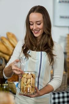 Personal femenino sonriente que sostiene un tarro de galletas en el mostrador
