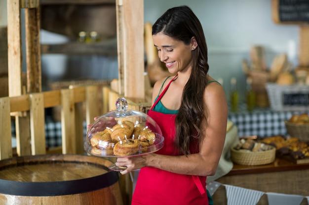 Personal femenino sonriente sosteniendo una bandeja de bocadillos en el mostrador