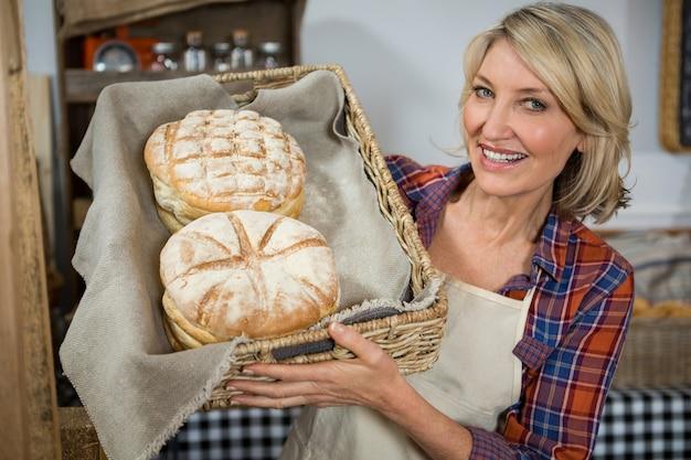 Personal femenino sonriente sosteniendo una cesta de mimbre de panes en el mostrador