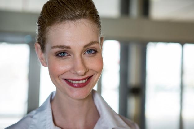 Personal femenino sonriente en la terminal del aeropuerto