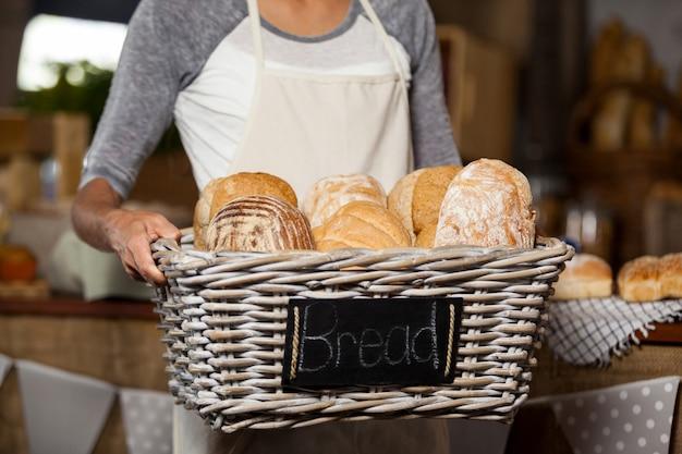 Personal femenino sosteniendo una cesta de mimbre de varios panes en el mostrador de la panadería
