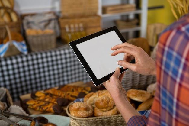 Personal femenino mediante tableta digital en el mostrador