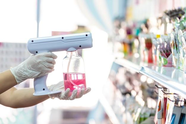 Personal con guantes usando máquina portátil de spray desinfectante fogger covid19 en la tienda