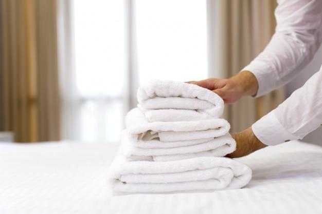 Personal del hotel preparando la almohada en la cama.