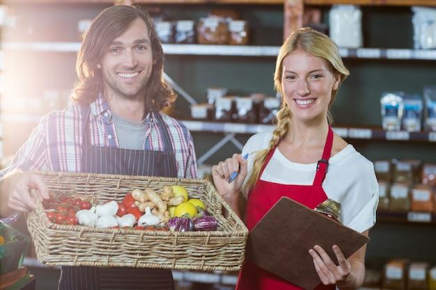 Personal masculino con canasta de verduras y personal femenino con portapapeles