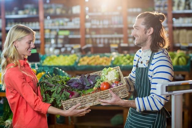 Personal masculino dando una caja de verduras frescas a la mujer en la sección orgánica