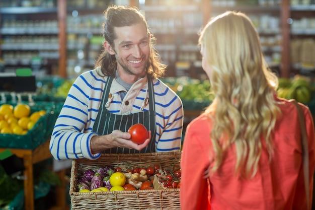 Personal masculino que ayuda a la mujer a seleccionar verduras frescas